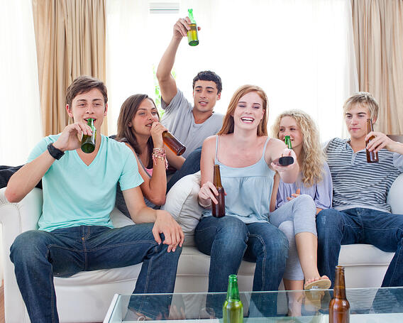Young friends drinking beer and watching tv at home